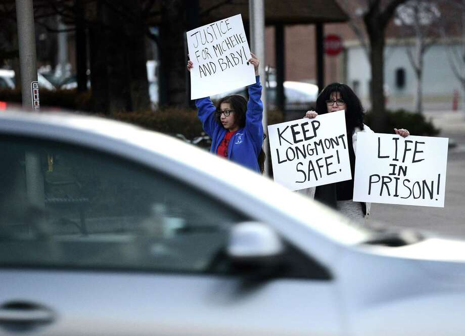 Eileen Egger, right, holds a sign with her granddaughter Naomi Garcia, 11, while cars pass by during a protest against Dynel Lane on Thursday, March 19, 2015, in Longmont, Colo. Lane is accused of stabbing a pregnant woman in the stomach and removing her baby, while the expectant mother visited her home to buy baby clothes advertised on Craigslist authorities said. The baby did not survive. (AP Photo/The Daily Camera, Jeremy Papasso) NO SALES Photo: AP / The Daily Camera