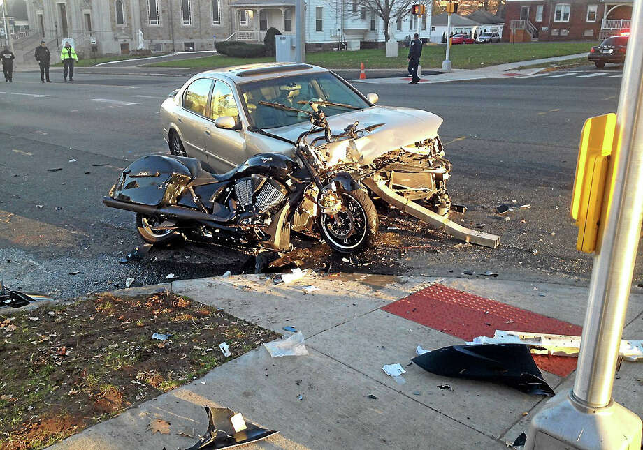 A motorcycle and sedan collided late Tuesday afternoon at the intersection of Washington and Pearl streets in Middletown, seriously injuring the driver of the Victory cruising bike. Photo: Jeff Mill — The Middletown Press