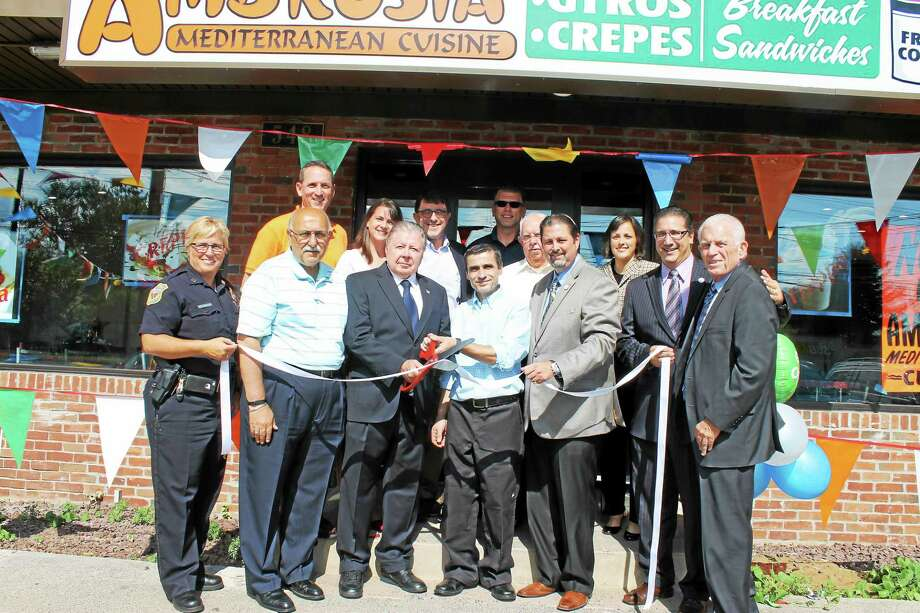 A grand opening for Ambrosia Mediterranean restaurant in Cromwell was held July 23. Those who joined in were, from left: Cromwell Police Capt. Denise Lamontagne, Town Manager Anthony Salvatore (front), state Sen. Paul Doyle (rear), state Rep. Christie Carpino, Cromwell Division Chairman Jay Polke, Town Planner Stuart Popper, Ambrosia Owner Arben Cela, Rodney Bitgood of Cromwell Automotive (rear), Councilman Allan Spotts, Mayor Enzo Faienza, Councilman Frank Emanuele, and Chamber President Larry McHugh. Photo: Courtesy Photo