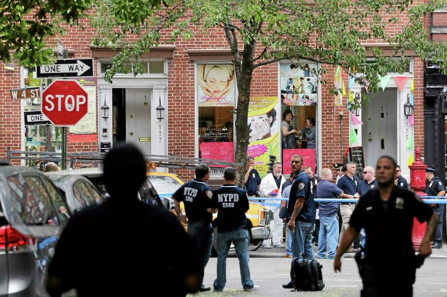 Police officers stand guard at the scene of a shooting, Monday, July 28, 2014, in the Greenwich Village neighborhood in New York. Authorities said a sex-assault suspect got in a shootout with law enforcement in New York City that left the suspect dead and two federal marshals and a police officer wounded. Photo: Mark Lennihan — The Associated Press  / AP