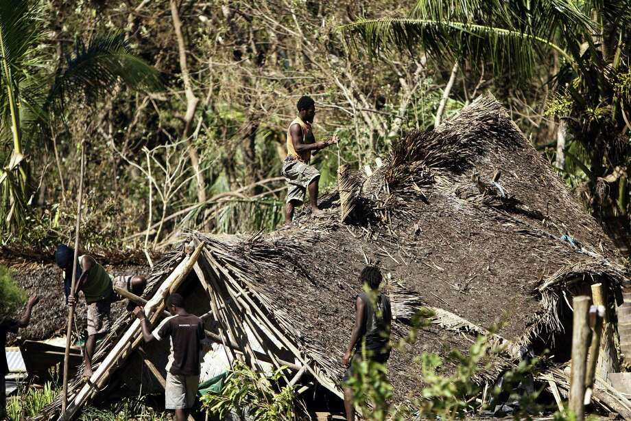 Young men take apart a hut destroyed by Cyclone Pam, Thursday, March 19, 2015, on Tanna Island, Vanuatu. Tanna Island in the southern part of the Vanuatu archipelago was one of the hardest hit when Cyclone Pam tore through the South Pacific nation early Saturday. The cyclone's 270 kilometer (168 mile) per hour winds pummeled lush tropical forests on Tanna into a brown jumble of broken trunks and strewn branches. (AP Photo/Nick Perry) Photo: AP / AP