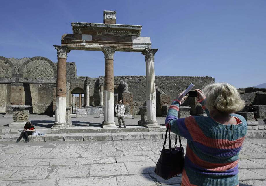 Tourists take pictures at the Pompeii ancient site near the Villa of Mysteries on the occasion of its presentation to journalists in Pompeii, Italy, Friday, March 20, 2015. Italy unveiled the restored crown jewel of the ancient city of Pompeii, the Villa of Mysteries, on Friday, showing off a rare success story as it races to shore up the site that has been marred by such mismanagement that it risked losing EU funding and being delisted as a UNESCO world heritage site. (AP Photo/Gregorio Borgia) Photo: AP / AP