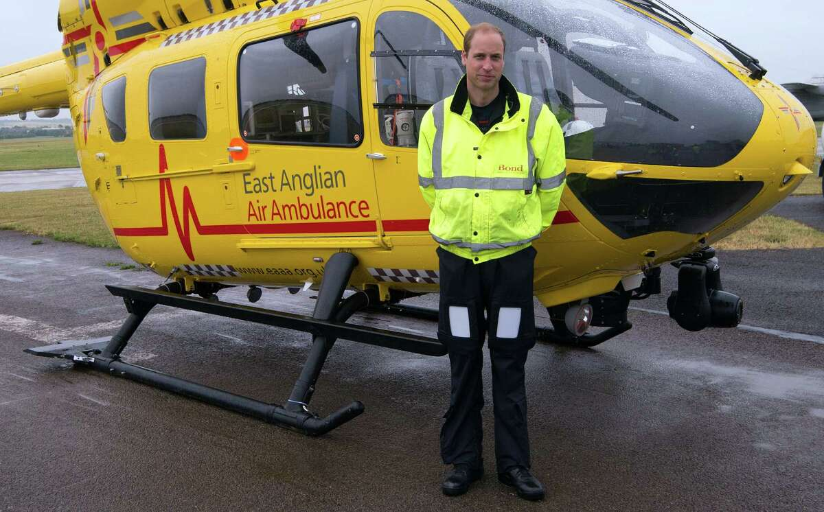 Britain's Prince William, the Duke of Cambridge poses in front of an East Anglian Air Ambulance (EAAA) as he begins his new role at Cambridge Airport, Cambridge, in England on July 13, 2015.