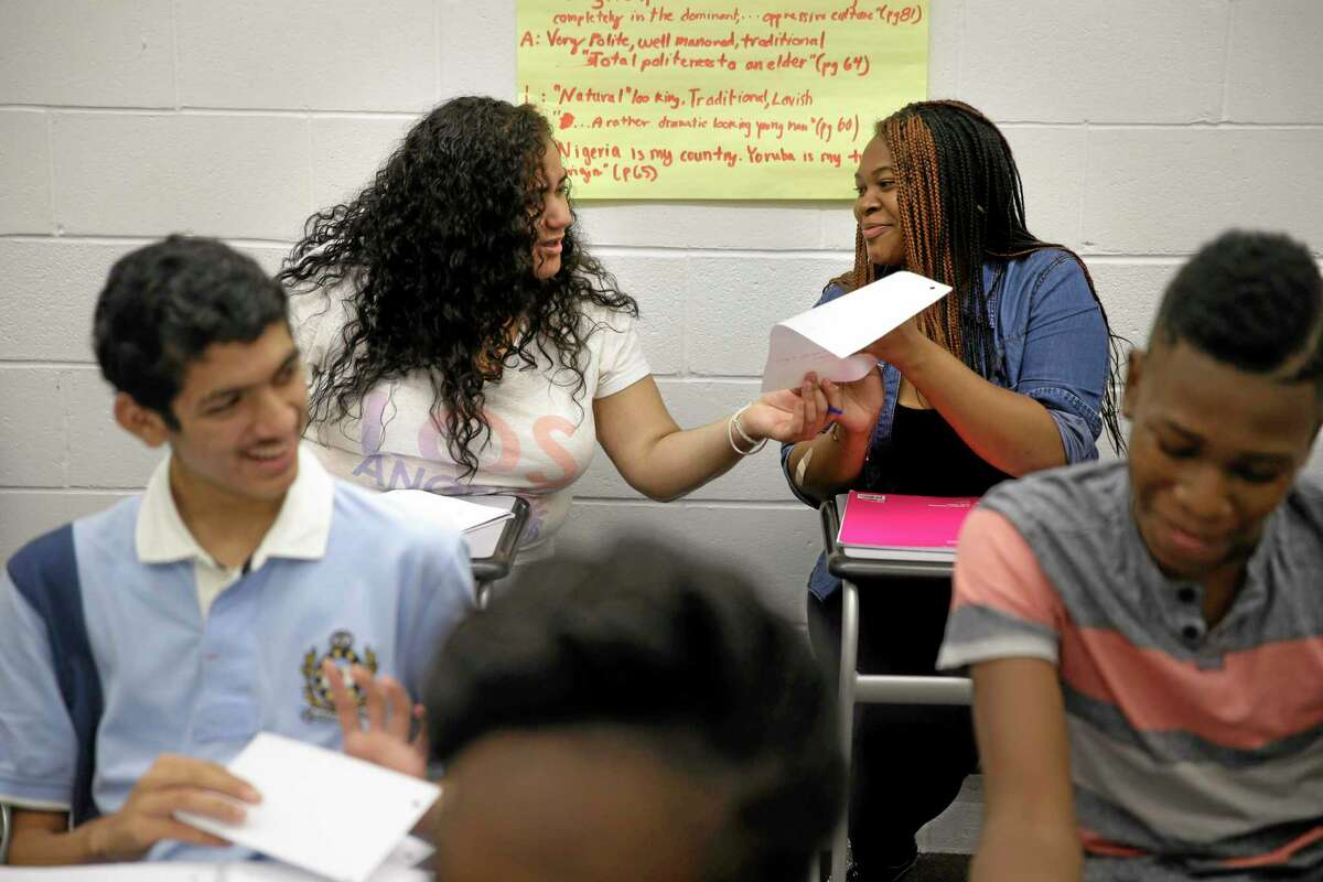 In this July 16, 2014 photo, Crystal Martinez, 18, second from left, and Reina Baltazar, 17, second from right, look at each others papers during their English class at an Upward Bound program in New York. This summer marks the 50th anniversary of Upward Bound, which was founded as an experimental program in 1964 as part of Lyndon B. Johnson's War on Poverty with a goal of helping students from low-income families get a college education. (AP Photo/Seth Wenig)