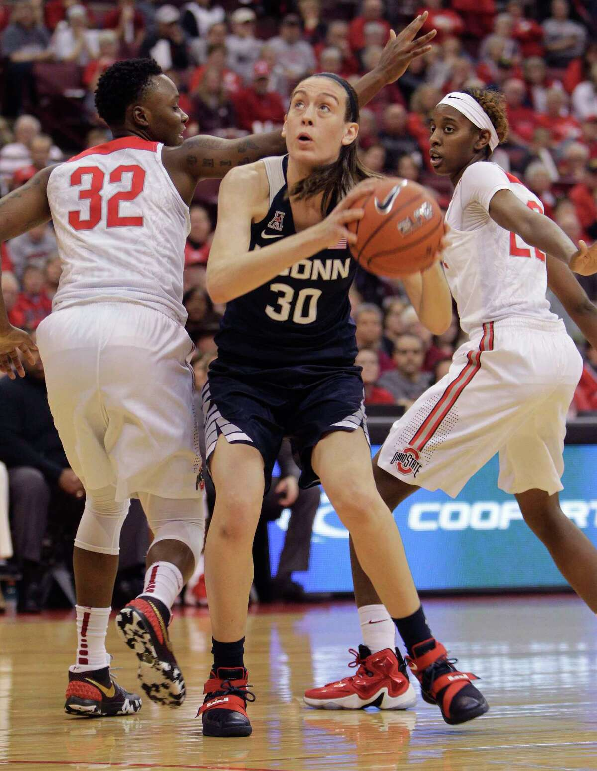 UConn's Breanna Stewart, center, drives to the basket between Ohio State's Shayla Cooper, left, and Alexa Hart during the first quarter Monday.