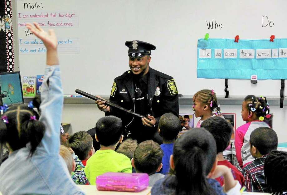 Police officer Issac Johnson talks with first-graders during Career Day at Bielefield School on Friday. Photo: Kathleen Schassler — The Middletown Press  / Kathleen Schassler All Rights