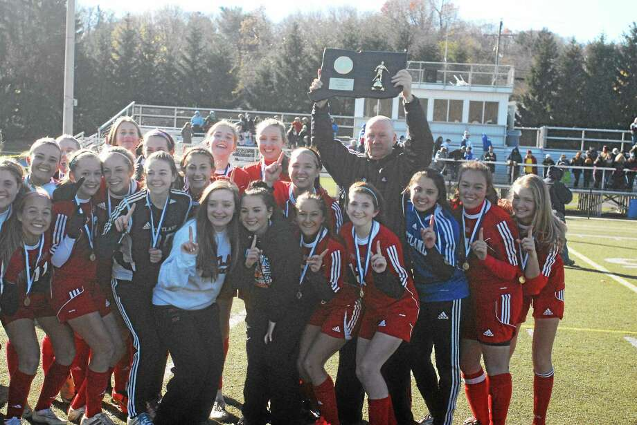 Portland girls soccer coach Sandy Booth holds up the state championship plaque after the Highlanders 2-1 win over Housatonic Saturday at Waterburyís Municipal Stadium. Photo: Jimmy Zanor — Middletown Press