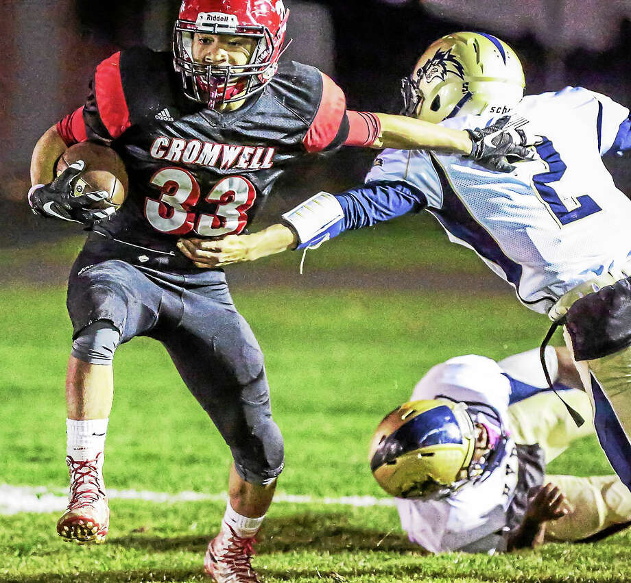 Cromwell's Kristian Sapp skips out of the tackle attempt by Hyde's Tyrese Thomas during the Panther's 33-12 win over Hyde this weekend in Cromwell. Photo: John Vanacaore – Special To The Press  / John Vanacore