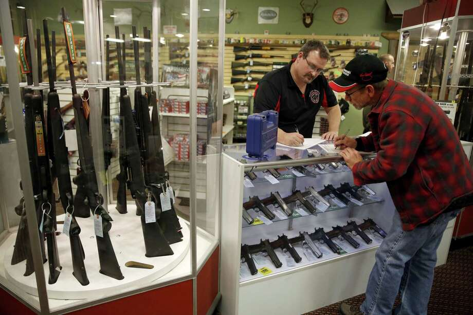 In this Nov. 15, 2014 photo, Steven King, left, fills out paperwork before selling a handgun to first-time gun owner Dave Benne at Metro Shooting Supplies, in Bridgeton, Mo. King says heís sold two to three times more weapons in recent weeks than normal as a grand jury decides whether to indict Ferguson police Officer Darren Wilson in the shooting death of Michael Brown. Photo: AP Photo/Jeff Roberson  / AP