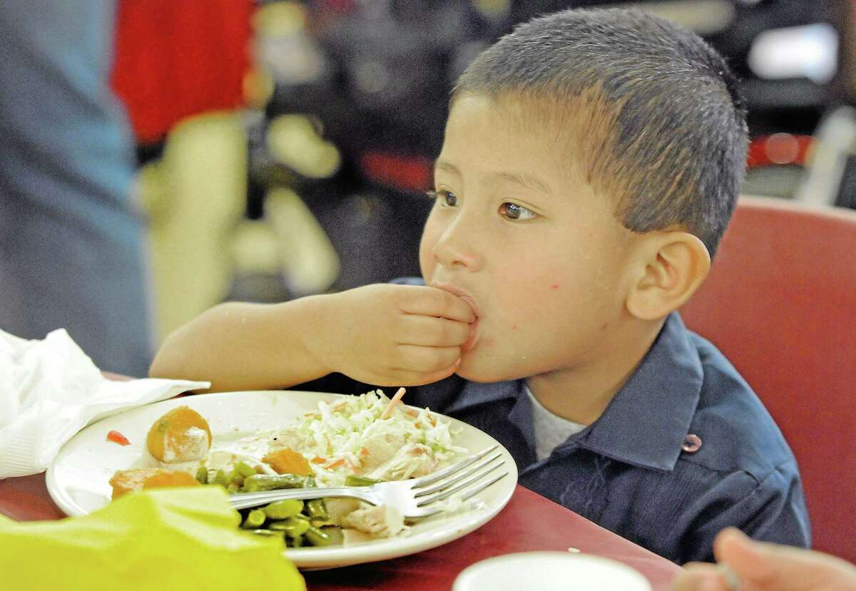 Javier Garcia, 3, of West Chester, Pa., eats during the 29th annual Thanksgiving Dinner celebration at the West Chester Senior Center.
