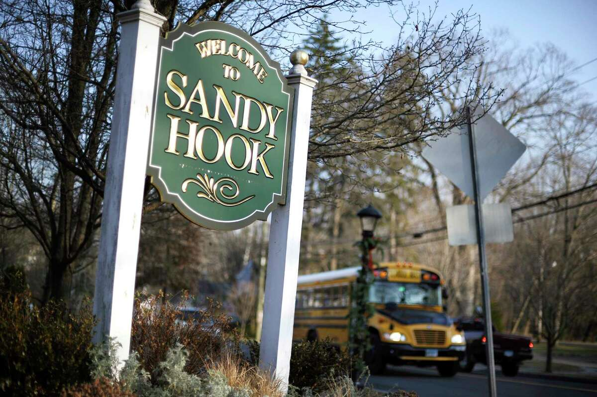 In this Dec. 4, 2013 photo, a school bus drives past a sign reading Welcome to Sandy Hook, in Newtown, Conn., where 26 people were killed by a gunman inside Sandy Hook Elementary School.
