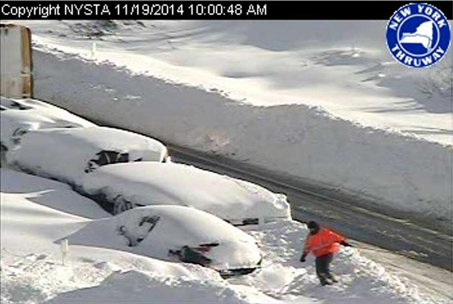 In this photo from a surveillance camera operated by the New York State Thruway Authority, a person climbs through piles of snow next to abandoned vehicles on the Thruway, near Lackawanna, N.Y., Wednesday, Nov. 19, 2014. A 132-mile stretch of the state Thruway in western New York remains closed as authorities continue their efforts to rescue motorists stranded on a Buffalo-area section of the highway. (AP Photo/New York State Thruway Authority) Photo: AP / New York State Thruway Authority