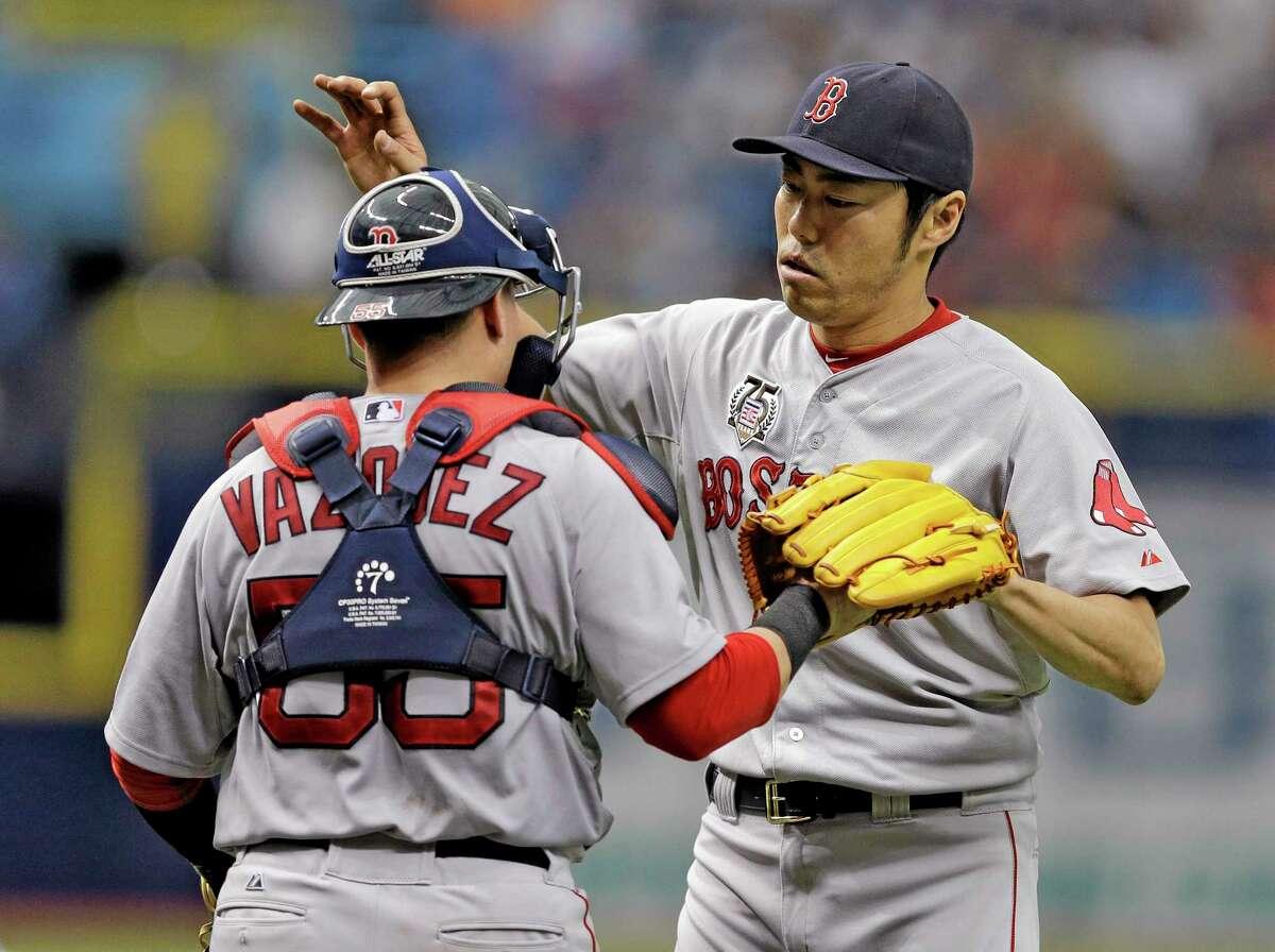 Red Sox closer Koji Uehara, left, hugs catcher Christian Vazquez after Boston's win over the Rays on Sunday.