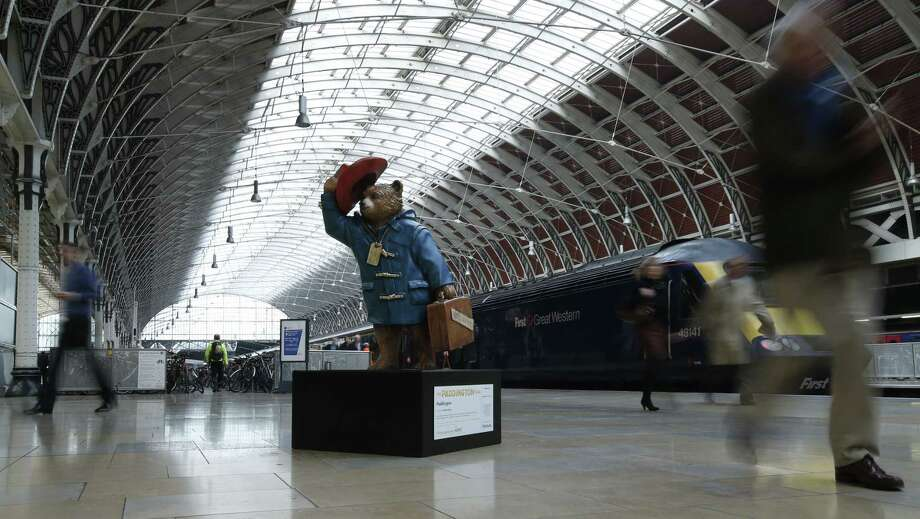 """Commuters alighting from a train pass by a statue of 'Paddington Bear' on the platform at Paddington railway station in London, Wednesday, Nov. 19, 2014. The creator of Paddington Bear, children's books, Michael Bond, has said he is """"amazed"""" that authorities found mild adult content in a film version of the famous British children's books. The British Board of Film Classification gave the """"Paddington"""" movie a parental guidance rating, saying the film contained """"dangerous behavior, mild threat, mild sex references and mild bad language."""" The bear's 88-year-old creator Michael Bond said he had not yet seen the film, but told the British Daily Mail newspaper that he couldn't imagine what the sex references were. The authority on Tuesday amended """"mild sex references"""" to """"innuendo"""" after the movie's distributor expressed unease. (AP Photo/Alastair Grant) Photo: AP / AP"""