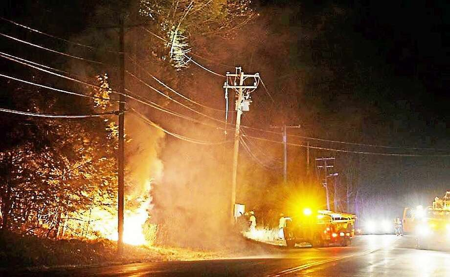 A snapped power cable sparked a fire that shut down part Route 81 in Haddam Tuesday night. Once the power was shut off, crews were able to extinguish the smoldering debris. Photo: (Contributed Photo -- Haddam Volunteer Fire Company)