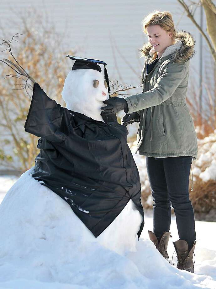 """Catherine Avalone - The Middletown Press """"I'm a Feb,"""" said Devin MacDonald as she carves in a smile on her """"snow grad."""" MacDonald, a resident of Portland graduated with a bachelor degrees in English and French on Saturday, Feb. 1 from Middlebury College in Vermont. """"After receiving our diploma and Painter's Cane, we ski down the front run at Snow Bowl to symbolize our graduation. I wore a blue boa."""" The 23-year-old said, """"Middlebury is known for one of the most unique graduation traditions in the country."""" Photo: Catherine Avalone — The Middletown Press / TheMiddletownPress"""