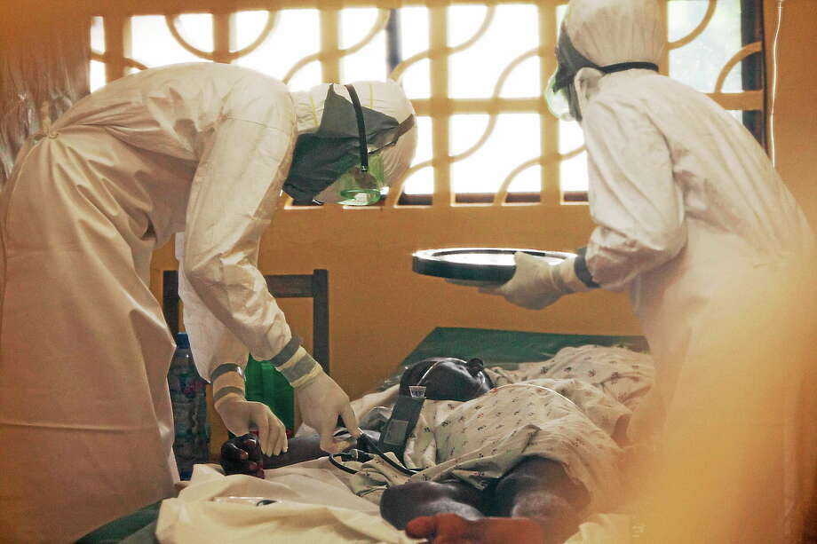 In this 2014 photo provided by the Samaritan's Purse aid organization, Dr. Kent Brantly, left, treats an Ebola patient at the Samaritan's Purse Ebola Case Management Center in Monrovia, Liberia. Photo: AP Photo/Samaritan's Purse  / Samaritan's Purse