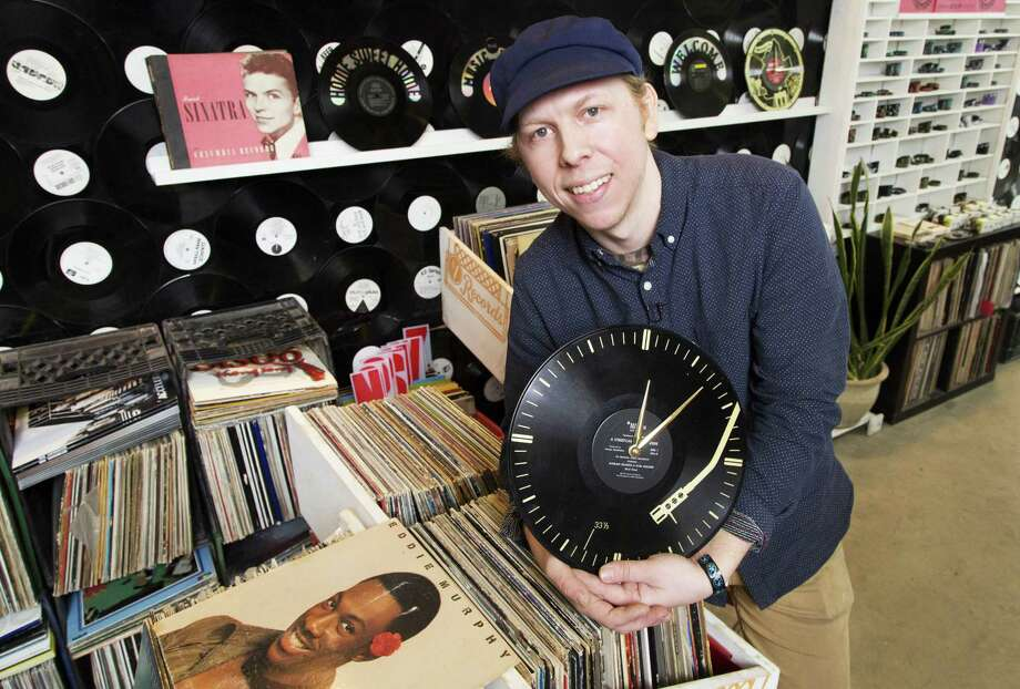 Patrick Chirico, owner of Wrecords By Monkey, poses with a clock his company has made from a recycled record at his production shop in the Brooklyn borough of New York. Chirico gets his raw materials from the surplus of used-record stores. Photo: Mark Lennihan — The Associated Press Photos  / AP