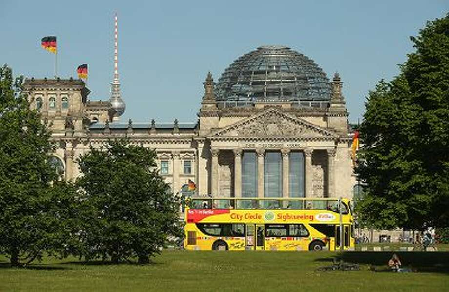 People relax on the lawn in front of the Reichstag as a tourist sightseeing bus passes by on May 15, 2013 in Berlin, Germany. Photo: Getty Images / 2013 Getty Images