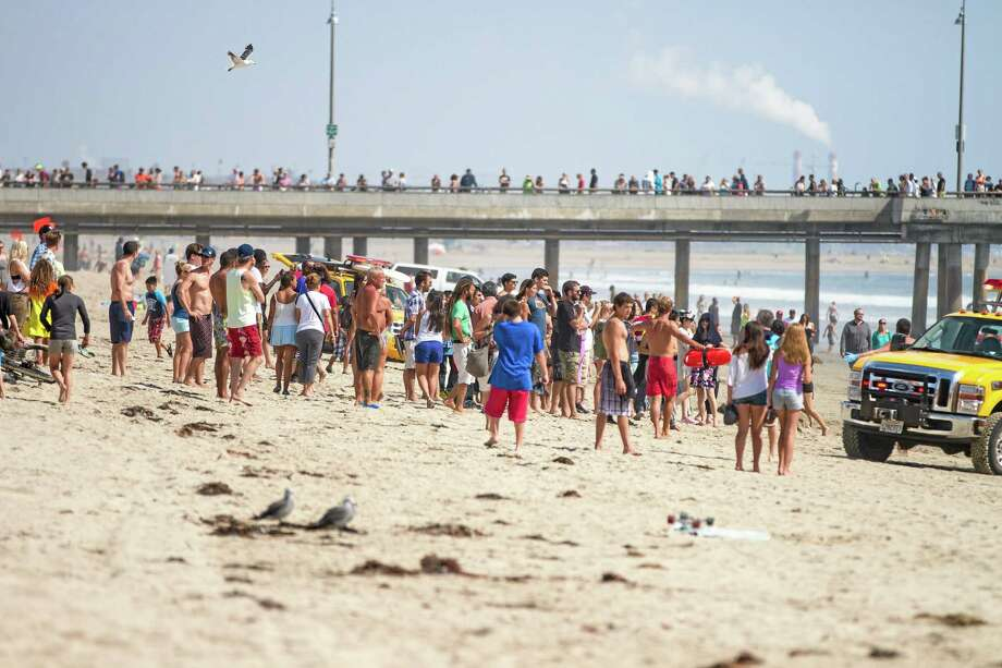 Pedestrians and beachgoers stand on the shore near Venice Beach as lifeguards, right, bring in a swimmer rescued from the water after a lightning strike Sunday in Los Angeles. Photo: Associated Press  / AP