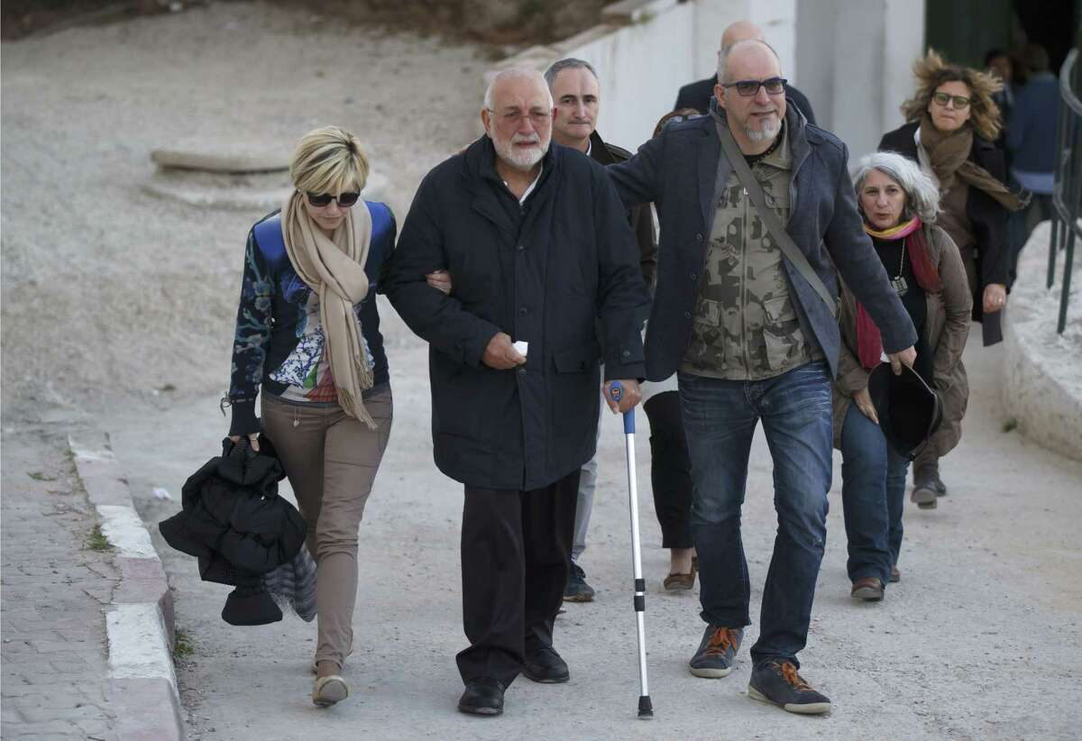 A unidentified Italian relative of a victim of the Tunis museum attack, center, is helped by Italian embassy staff , as he leaves the morgue of the Charles Nicolle hospital in Tunis Tunisia, Thursday, March 19, 2015. The radical Islamic State Group claimed responsibility Thursday for the attack on a famed Tunis museum that left 23 people dead. (AP Photo/Michel Euler)