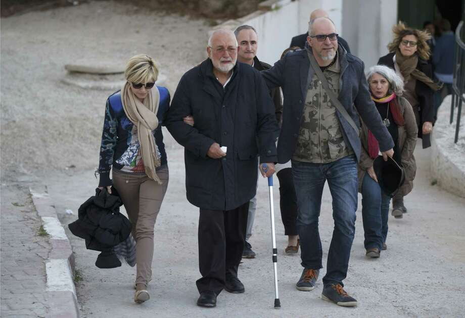 A unidentified Italian relative of a victim of the Tunis museum attack, center, is helped by Italian embassy staff , as he leaves the morgue of the Charles Nicolle hospital in Tunis Tunisia, Thursday, March 19, 2015. The radical Islamic State Group claimed responsibility Thursday for the attack on a famed Tunis museum that left 23 people dead. (AP Photo/Michel Euler) Photo: AP / AP