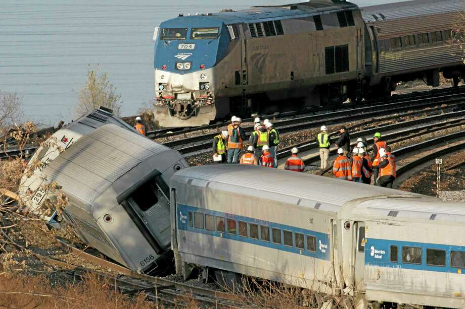 FILE - In this Dec. 1, 2013 file photo, an Amtrak train, top, traveling on an unaffected track, passes a derailed Metro North commuter train in the Bronx borough of New York. Senators say theyíre frustrated with the governmentís slow pace at writing new rail safety regulations in light of recent fiery freight train accidents and a deadly commuter train derailment. Sen. Richard Blumenthal, D-Conn., warned witnesses at a Senate hearing Thursday, ìone of the things we're going to do here is impose accountabilityî.  (AP Photo/Mark Lennihan, File) Photo: AP / AP