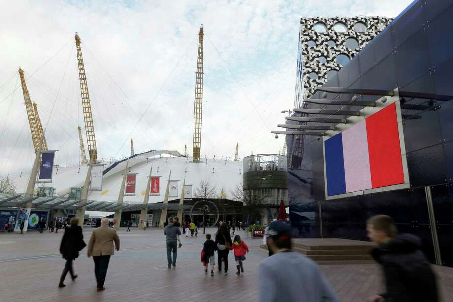 The French flag is displayed outside the O2 Arena as people arrive for the ATP World tour finals tennis, in solidarity with France after the deadly attacks in Paris. The Islamic State group claimed responsibility for Friday's attacks on a stadium, a concert hall and Paris cafes that left more than 120 people dead and over 350 wounded. Photo: AP Photo/Tim Ireland  / AP