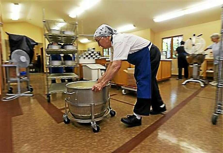In this Thursday, July 16, photo, Sister Patricia pushes a container of batter at New Skete Kitchens in Cambridge, N.Y. The nuns of New Skete lead a cloistered life marked by prayer, contemplation and baking cheesecakes, lots of cheesecake. Photo: AP Photo/Mike Groll  / AP
