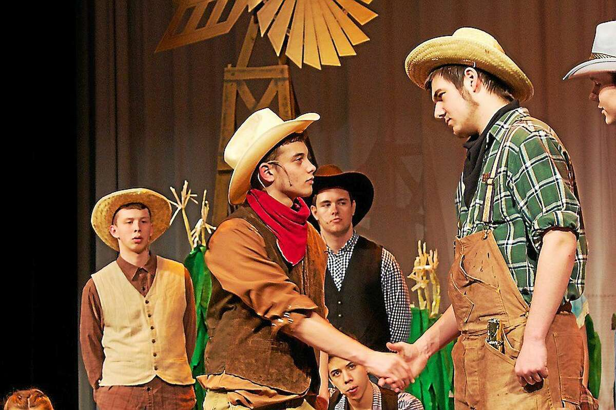 """CONTRIBUTED PHOTO BY STUART NOELTE Cast members look on as Curly (Josh Arroyo) and Judd (Mike Adams) create an uneasy peace in Portland High School's production of """"Oklahoma!"""""""