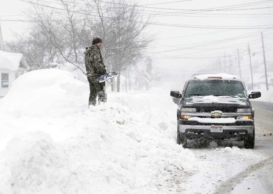 Jeremy Bauer stands on a snowbank next to a buried car outside his brother's house on Wednesday, Nov. 19, 2014, in Lancaster, N.Y. Lake-effect snow pummeled areas around Buffalo for a second straight day, leaving residents stuck in their homes as officials tried to clear massive snow mounds with another storm looming. Photo: (AP Photo/Mike Groll) / AP