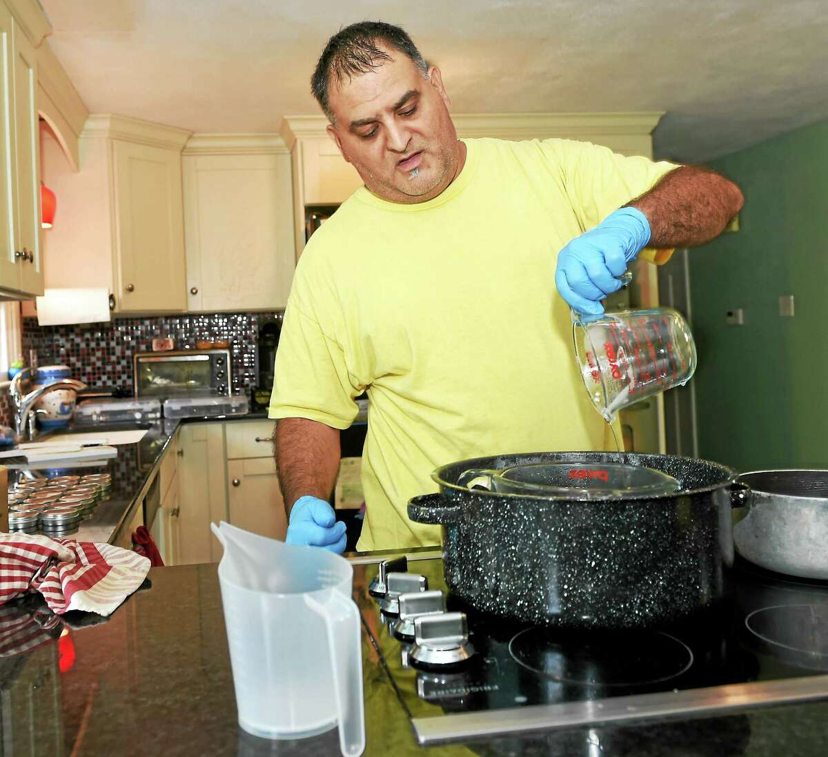 (Peter Hvizdak - New Haven Register) Chad Minervini of Durham, owner of Mini Bees, LLC, makes his own base oil for Buzzle Balm, an all natural lip balm, in his home kitchen. It took Minervini one-year working diligently to create his own formula for Buzzle Balm and his product line of body butters. Today he has 17 different flavors of lip balm. HIs company will soon introduce a line of bath salts, facial scrubs and body scrubs. Friday October 9, 2015.