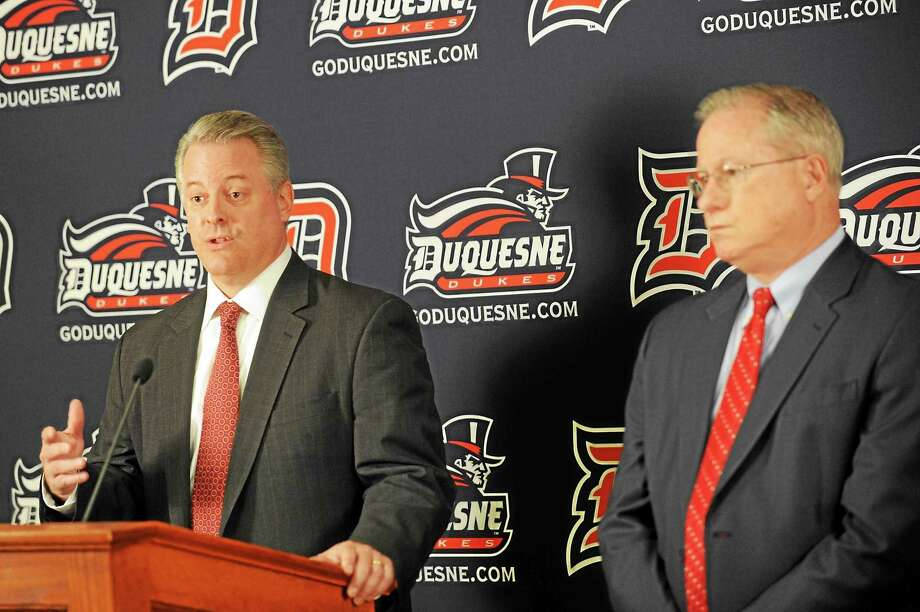 New Quinnipiac athletic director Greg Amodio, left, had to make the difficult decision to fire Duquesne men's basketball coach Ron Everhart back in 2012. At right is university president Charles J. Dougherty. Photo: Rebecca Droke — Pittsburgh Post-Gazette File Photo  / Pittsburgh Post-Gazette