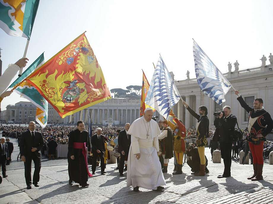 Pope Francis, center, walks past faithful wearing traditional costumes and holding flags as he arrives for his weekly general audience in St. Peter's Square, at the Vatican, Wednesday, March. 18, 2015. (AP Photo/Gregorio Borgia) Photo: AP / AP