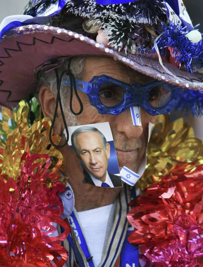 A supporter of Israeli Prime Minister Benjamin Netanyahu, on the photo, waits for his campaign rally to start in Tel Aviv, Israel, Sunday, March 15, 2015, two days ahead of parliament elections. Netanyahu seeks his fourth term as prime minister. (AP Photo/Oded Balilty) Photo: AP / AP