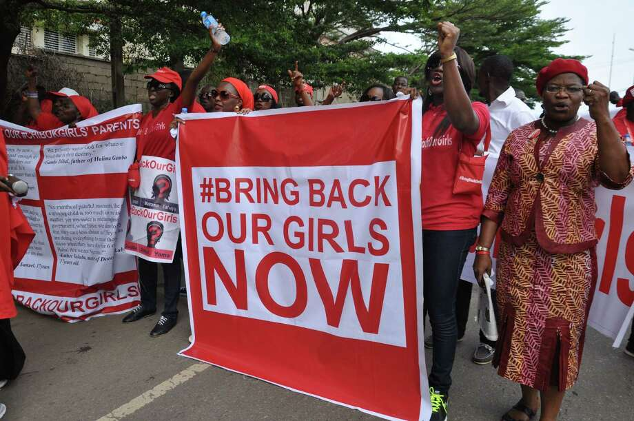 FILE - In this Tuesday Oct. 14, 2014 file photo, people demonstrate calling on the Nigerian government to rescue girls taken from a secondary school in Chibok region, in the city of Abuja, Nigeria. Nigeriaís military says it has no news of the more than 200 schoolgirls kidnapped by Islamic extremists nearly a year ago, despite liberating dozens of towns from the girlsí Boko Haram abductors. (AP Photo/Olamikan Gbemiga, File) Photo: AP / AP