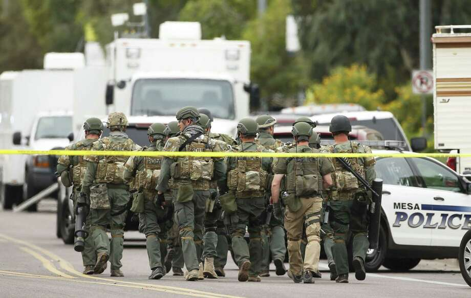 A SWAT team walks down the street near Adams Elementary School searching for a gunman on Wednesday, March 18, 2015 in Mesa, Ariz. A gunman wounded at least four people across multiple locations in the Phoenix suburb. The first shooting happened at a motel, and people were also wounded at a restaurant and nearby apartment complexes.  (AP Photo/The Arizona Republic, Rob Schumacher)  MARICOPA COUNTY OUT; MAGS OUT; NO SALES Photo: AP / The Arizona Republic