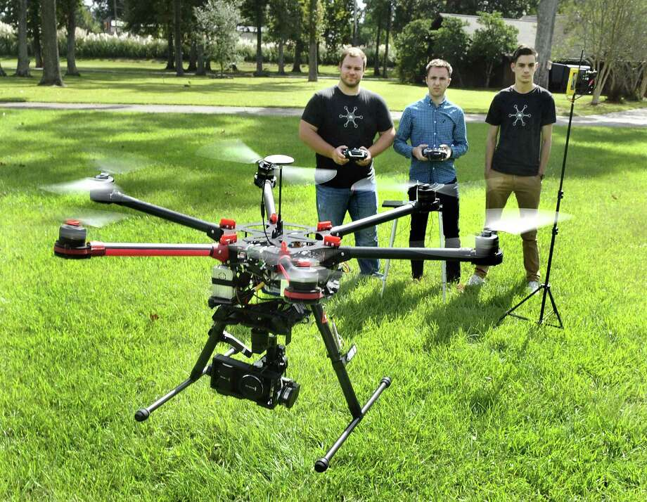 Paul Charbonnet, left, owner of the Baton Rouge company Atmosphere Aerial, and pilot/camera operators Josh Rogers, center and Cole Sullivan, right, demonstrate the use of the company's DJIS900 'hexa-copter,' the workhorse drone the company uses for aerial photography jobs.  It uses a lithium-polymer battery for power, can carry gimbal-mounted cameras. They choose to operate it only up to 1000 feet from their base station, keeping line-of-sight, for control and safety reasons.  Charbonnet says the company currently has more clients outside Louisiana than it does in the state, but hopes to develop more business here. (AP Photo/The Advocate,Travis Spradling) Photo: AP / The Baton Rouge Advocate