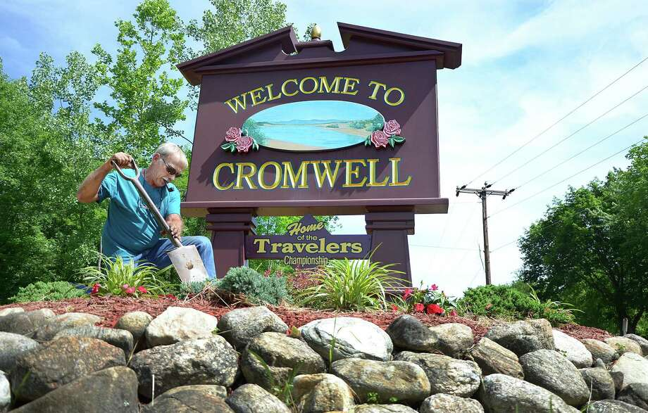 Bruce Cutkomp Sr., a landscaping foreman employed by A.J. Vicino & Sons Nursery in Rocky Hill, plants flowers at the Welcome to Cromwell sign on Main Street. Photo: Middletown Press File Photo