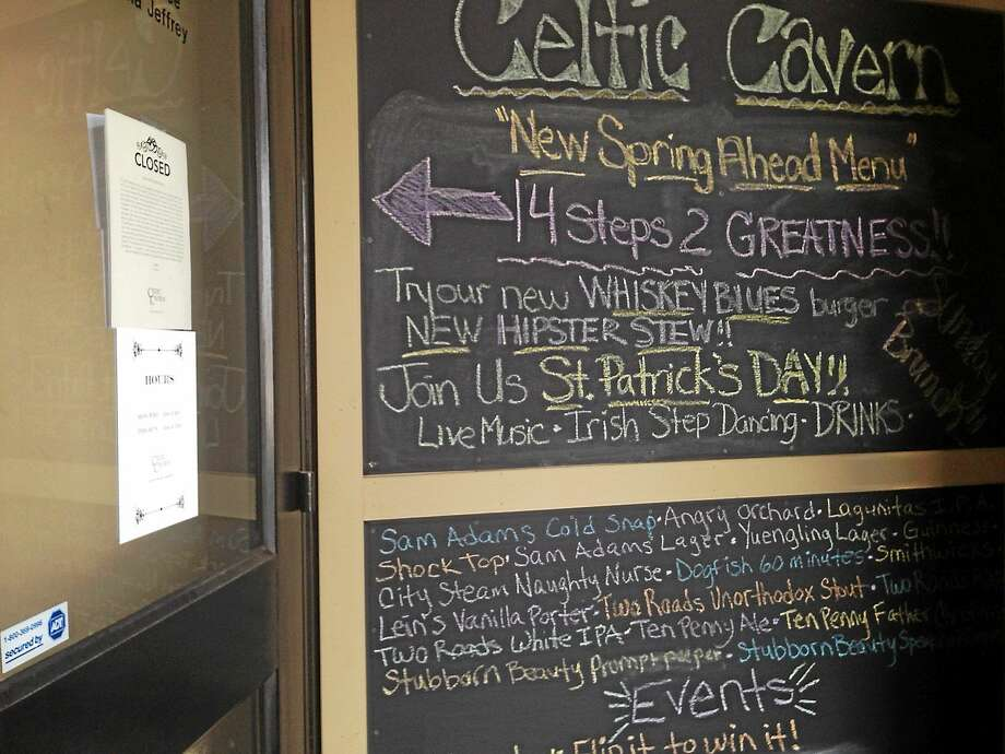 The Celtic Cavern door was locked on Tuesday, on St. Patrick's Day. The pub's daily specials were listed on signage outside of the entrance. Photo: Brian Zahn — The Middletown Press