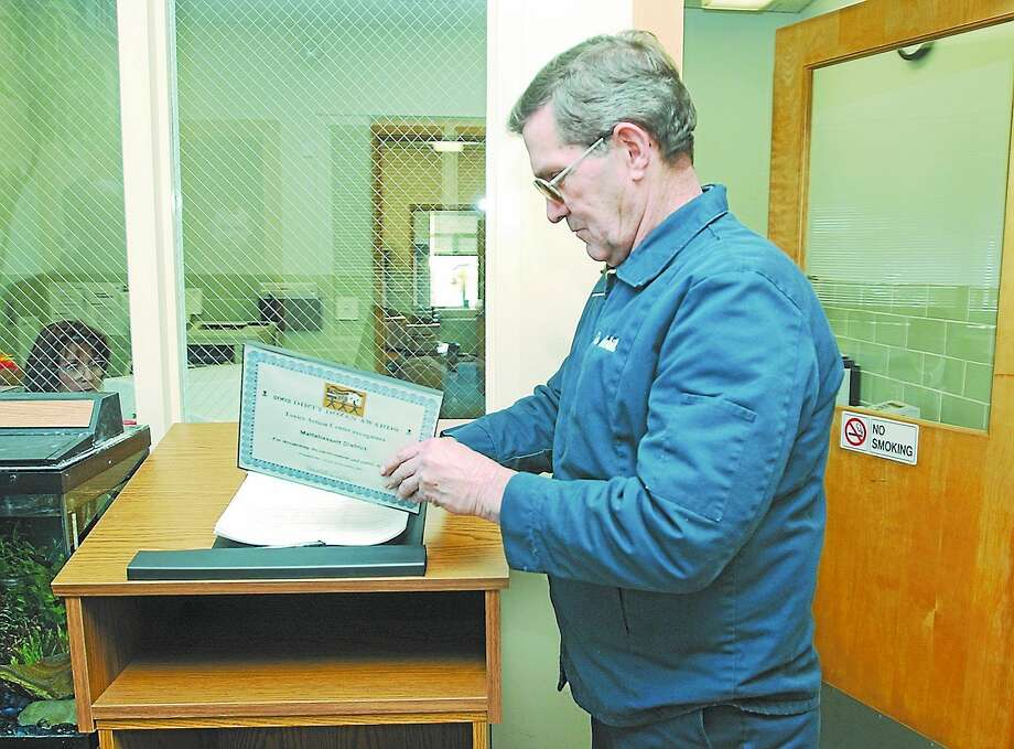 Middletown Press file photo Al Waters of Concerned Citizens of Cromwell places a 2002 Dirty Dozen Award on the guest book in the lobby of the Mattabassett District offices in Cromwell in this file photo. The Knights of Columbus has chosen Waters as the town's 2105 Man of the Year. Photo: Journal Register Co.