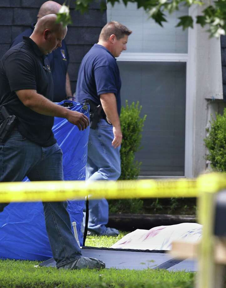Investigators work Thursday in the front yard of a home in Broken Arrow, Okla., where five people were discovered stabbed to death. Two teenagers were taken into custody. Photo: AP Photo/Sue Ogrocki / AP