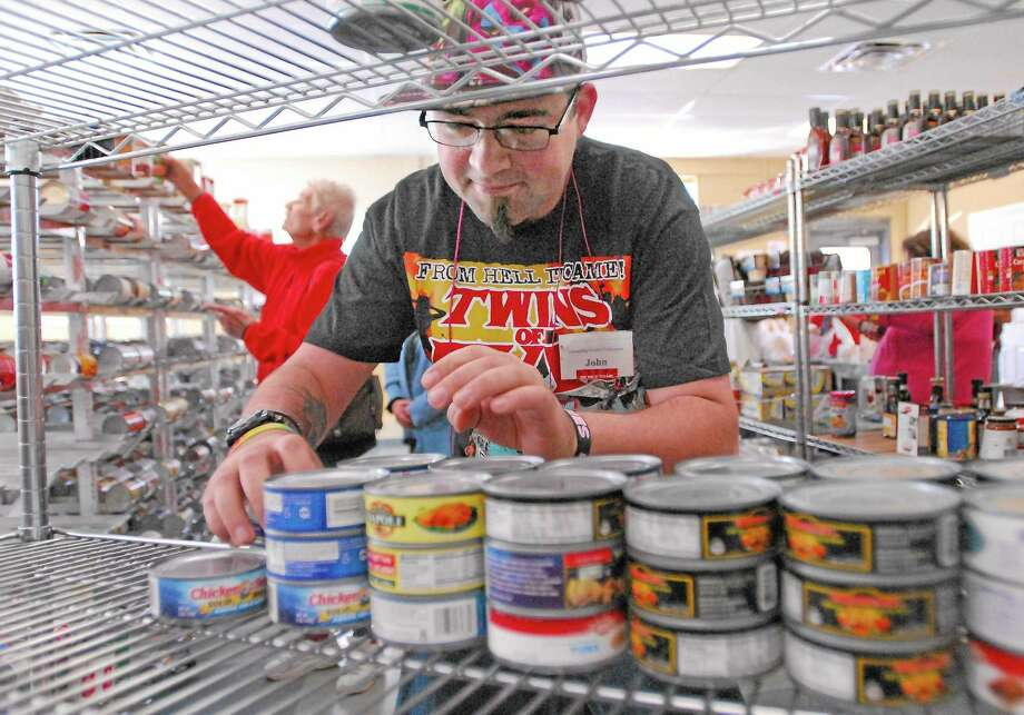 CATHERINE AVALONE/THE MIDDLETOWN PRESS ¬ Middletown resident John Kovach, a volunteer at Amazing Grace Food Pantry in Middletown  organizes cans of tuna fish before the Amazing Challenge Soup Supper. Photo: Journal Register Co.