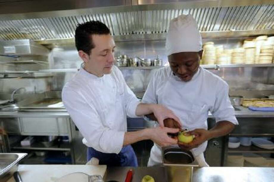 "French chef William Pradeleix (L) works with one of his apprentice cook Moussa Coulibaly on December 12, 2013 in his Paris' restaurant ""Manger."""