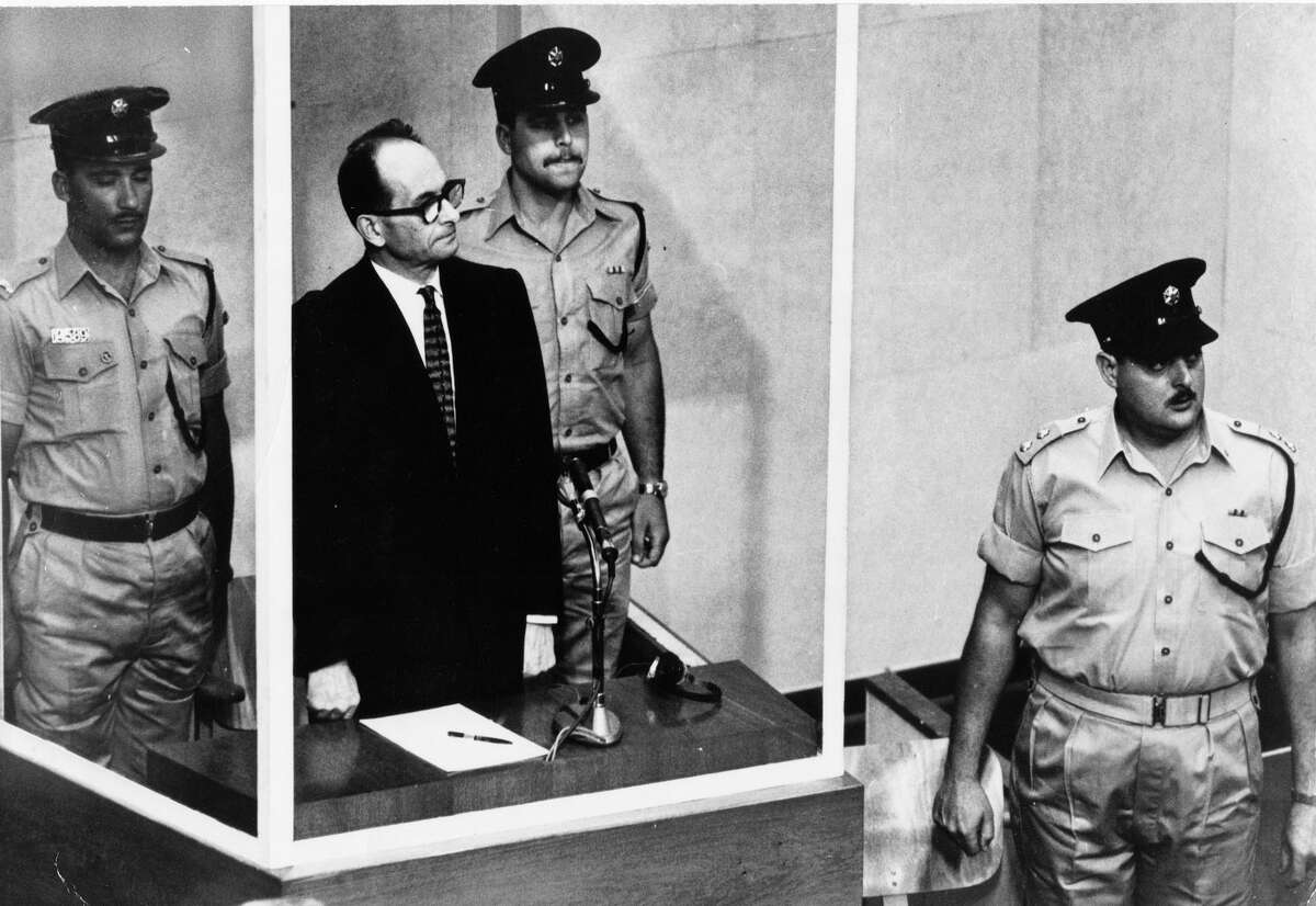 FILE - The 1961 file photo shows Adolf Eichmann standing in his glass cage in the Jerusalem courtroom where he was tried for war crimes committed during World War II. AP FILE Photo