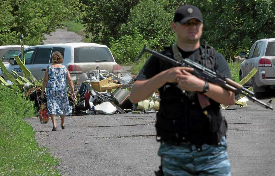A police officer stands guard as a woman walks past pieces of the crashed Malaysia Airlines Flight 17 in the village of Petropavlivka, Donetsk region, eastern Ukraine Friday, July 25, 2014. (AP Photo/Dmitry Lovetsky) Photo: AP / AP