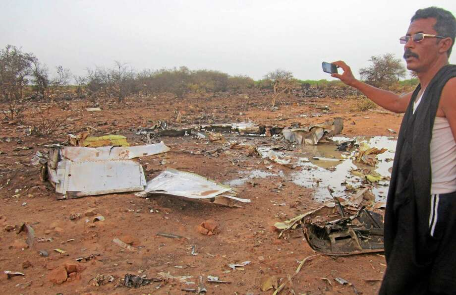 This photo provided on Friday, July 25, 2014,  by the Burkina Faso Military shows  a man at the site of the plane crash in Mali. French soldiers secured a black box from the Air Algerie wreckage site in a desolate region of restive northern Mali on Friday, the French president said. Terrorism hasn't been ruled out as a cause, although officials say the most likely reason for the catastrophe that killed all onboard is bad weather. At least 116 people were killed in Thursday's disaster, nearly half of whom were French. (AP Photo/Burkina Faso Military) Photo: AP / Burkina Faso Military