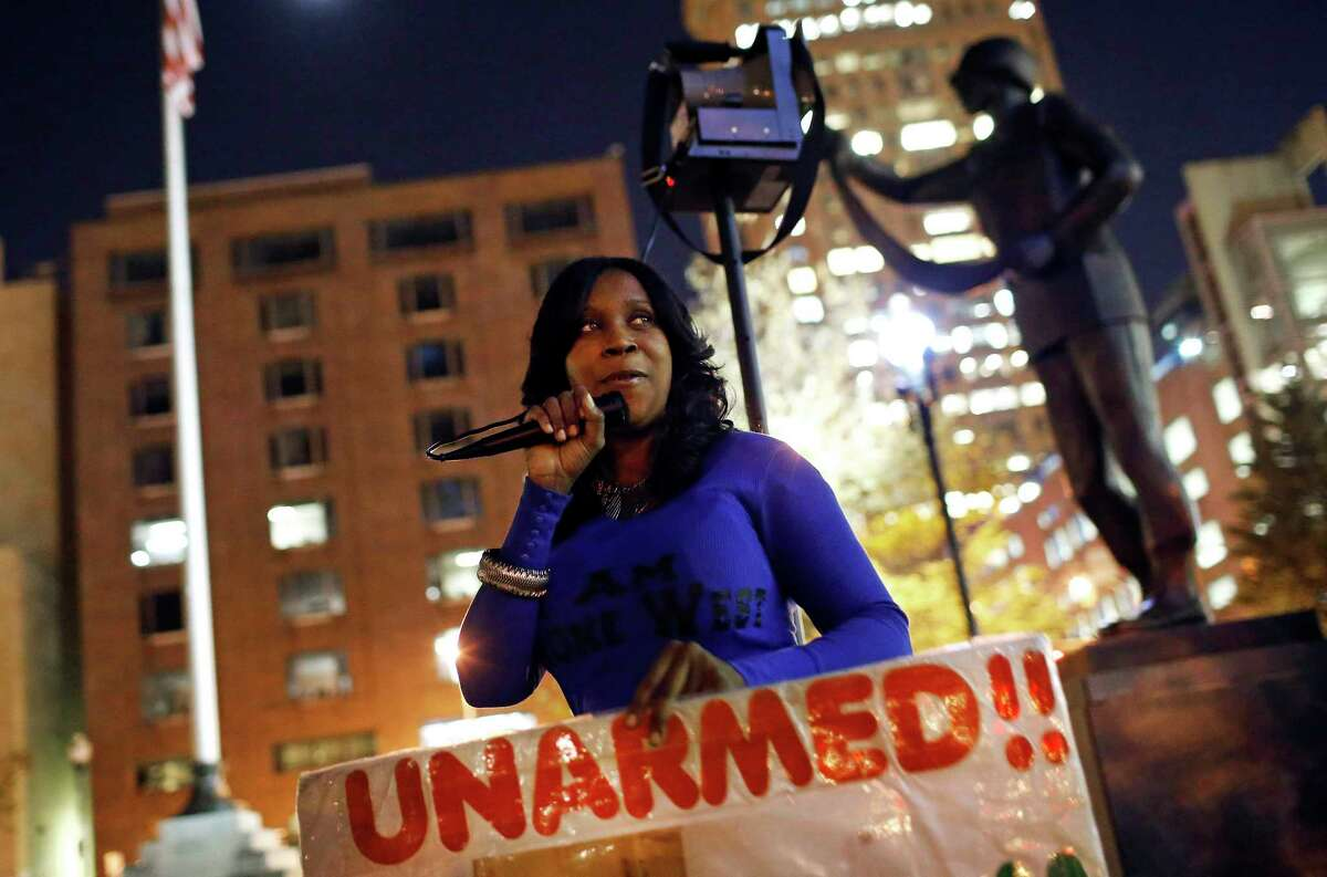 In this Oct. 21, 2015 picture, Tawanda Jones leads a vigil for her brother, Tyrone West, outside of Baltimore City Hall. West died under murky circumstances in July 2013 after an encounter with Baltimore police. Every Wednesday since then, Jones has stood vigil -- in front of City Hall, outside the state's attorney's office, on an East Baltimore street corner, in the freezing dark of winter, in the stifling heat of summer. Sometimes she is backed by supporters; sometimes she stands alone, a grim reminder of a deep divide between the police and the people of Baltimore.