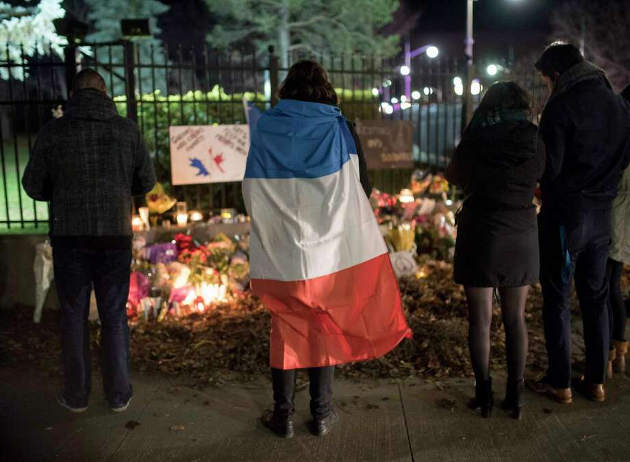 A person wears a French flag at a memorial outside the French Embassy, Saturday, Nov. 14, 2015, in Ottawa, Ontario, following deadly attacks in Paris on Friday. Photo: Justin Tang/The Canadian Press Via AP  / The Canadian Press