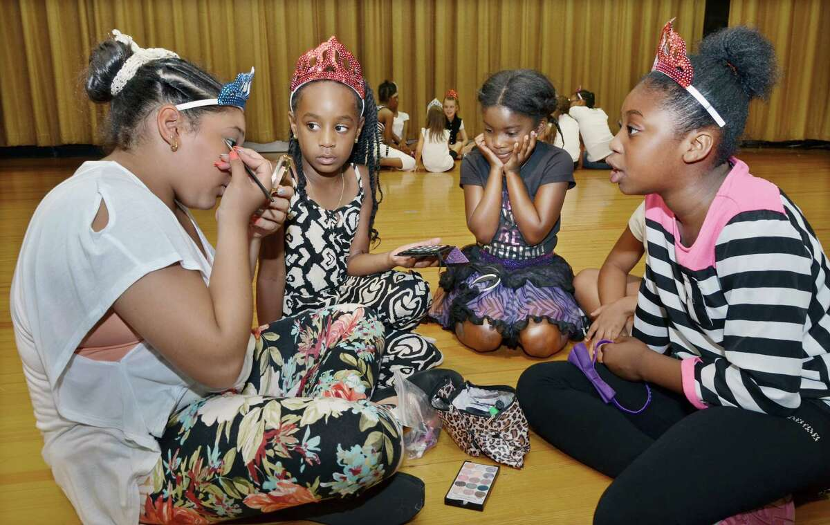 "Dancers in the Middletown Summer Dance Camp watch one of the older campers put on her own make-up shortly before their dance recital, ""New York, New York,"" at the Snow School auditorium Friday afternoon. Camp director Lynn Agnew and choreographers Haley McDonald, Alissa Lancia, Marisa Bishop, Cassidy Zanette, Caitlin Nelson and Lynn Agnew prepared the girls all week to put on a show for parents and guests."